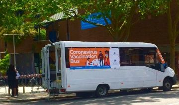 Vaccine Bus parked up with chairs on the pavement